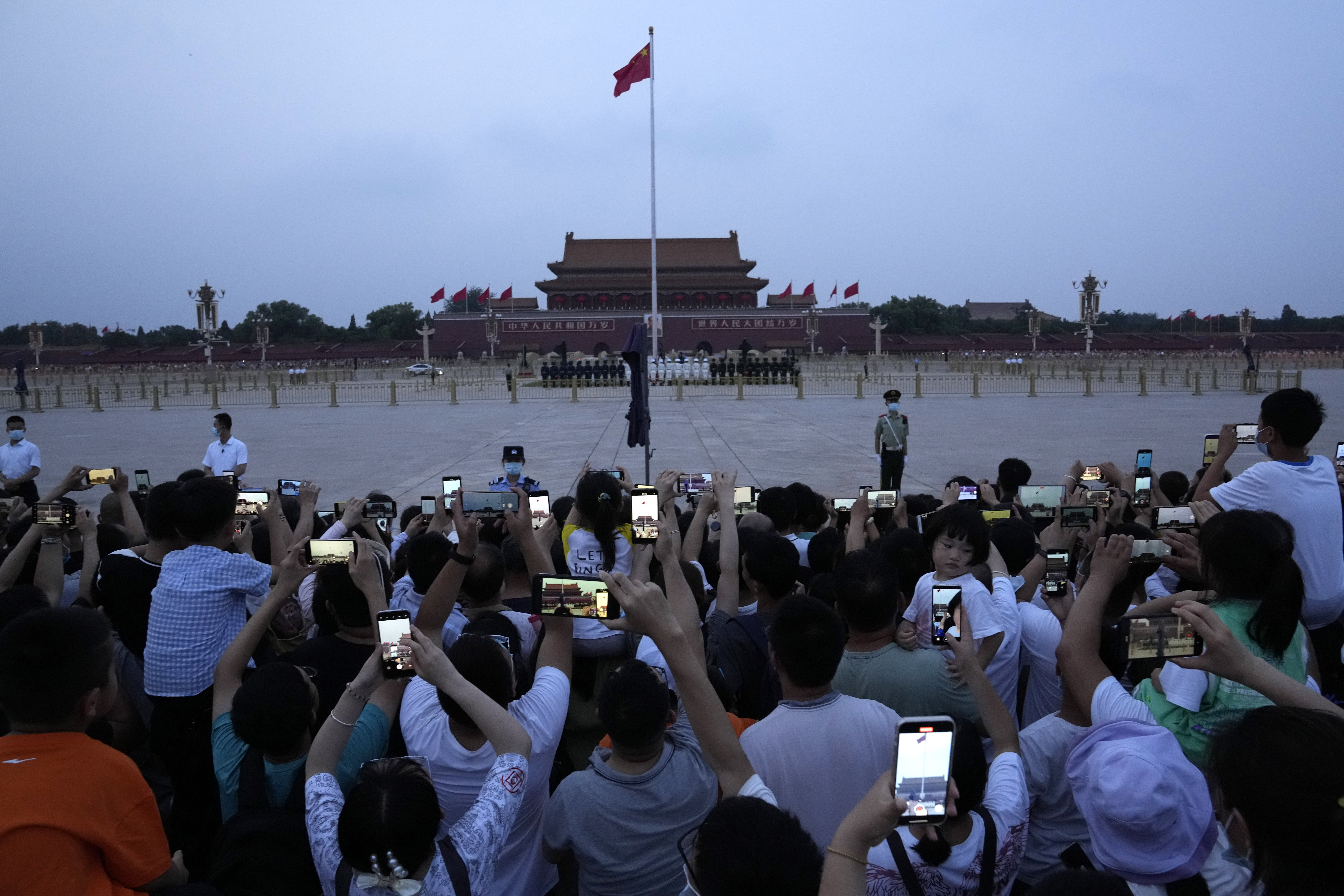 Residents gather to watch the flag lowering on Tiananmen Square in Beijing