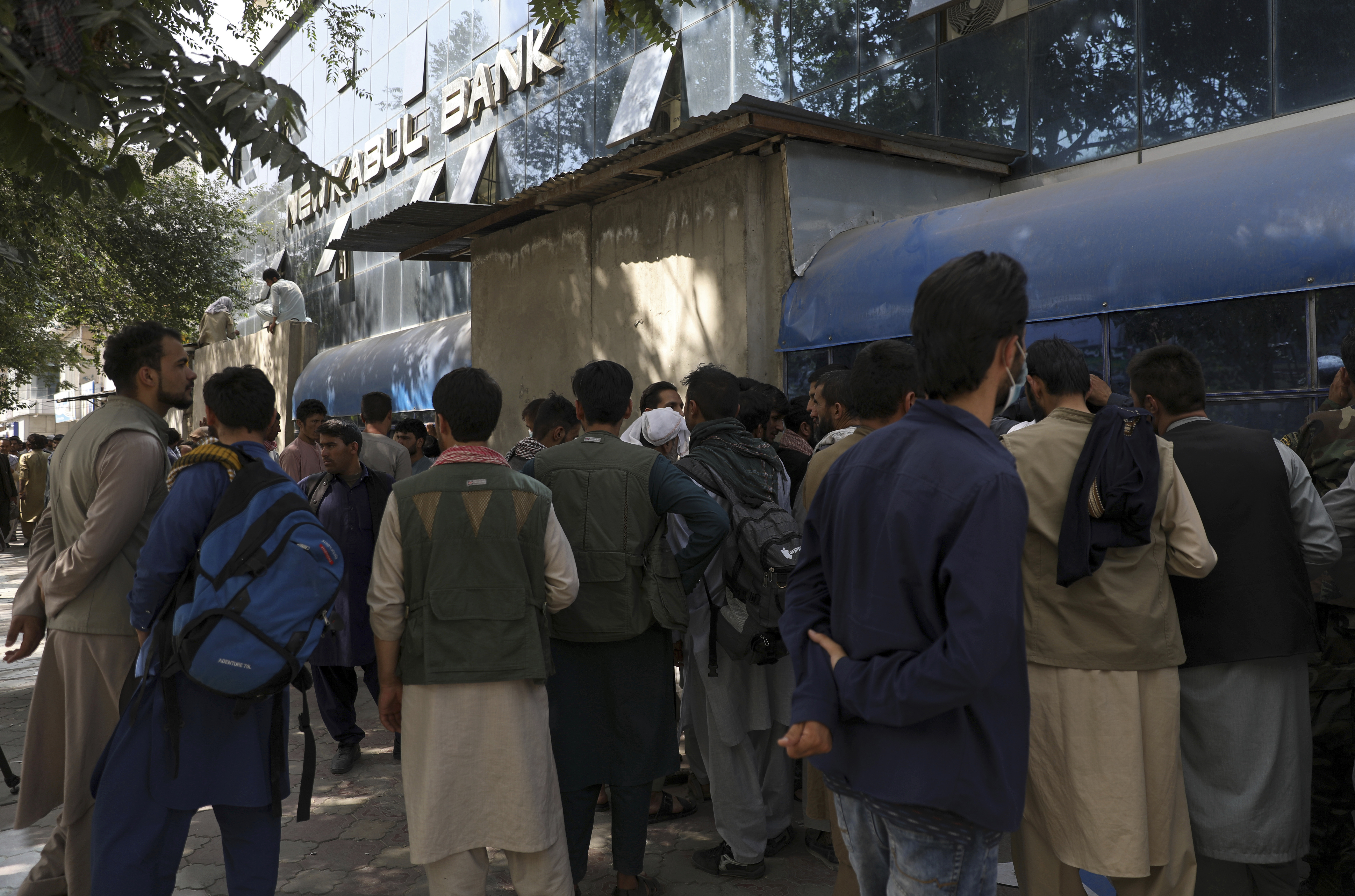 Photo: Afghans wait in long lines for hours to try to withdraw money, in front of Kabul Bank, in Kabul, Afghanistan, Sunday, Aug. 15, 2021. Officials say Taliban fighters have entered Kabul and are seeking the unconditional surrender of the central government. (AP Photo/Rahmat Gul)