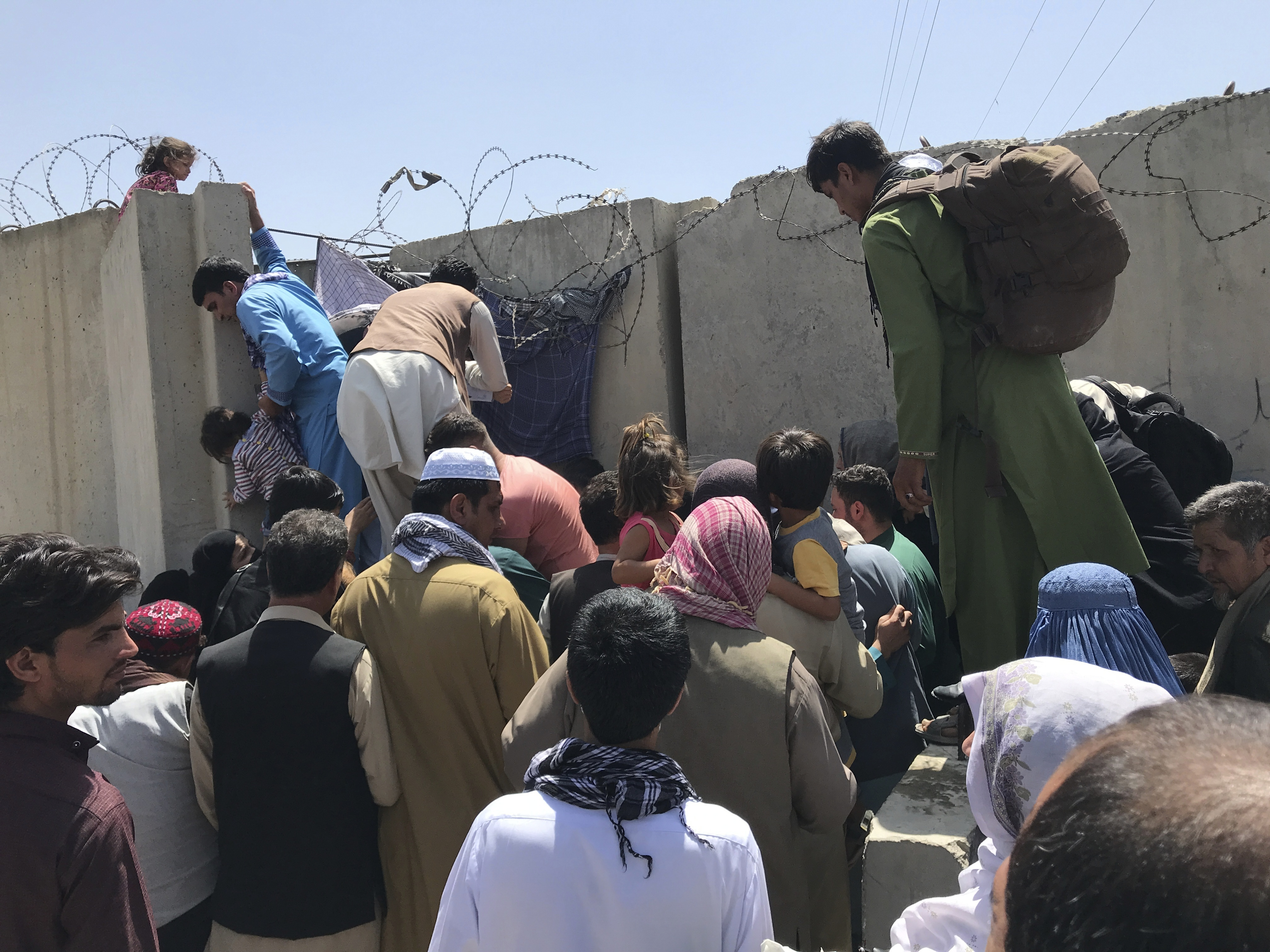 People struggle to cross the boundary wall of Hamid Karzai International Airport in Kabul.