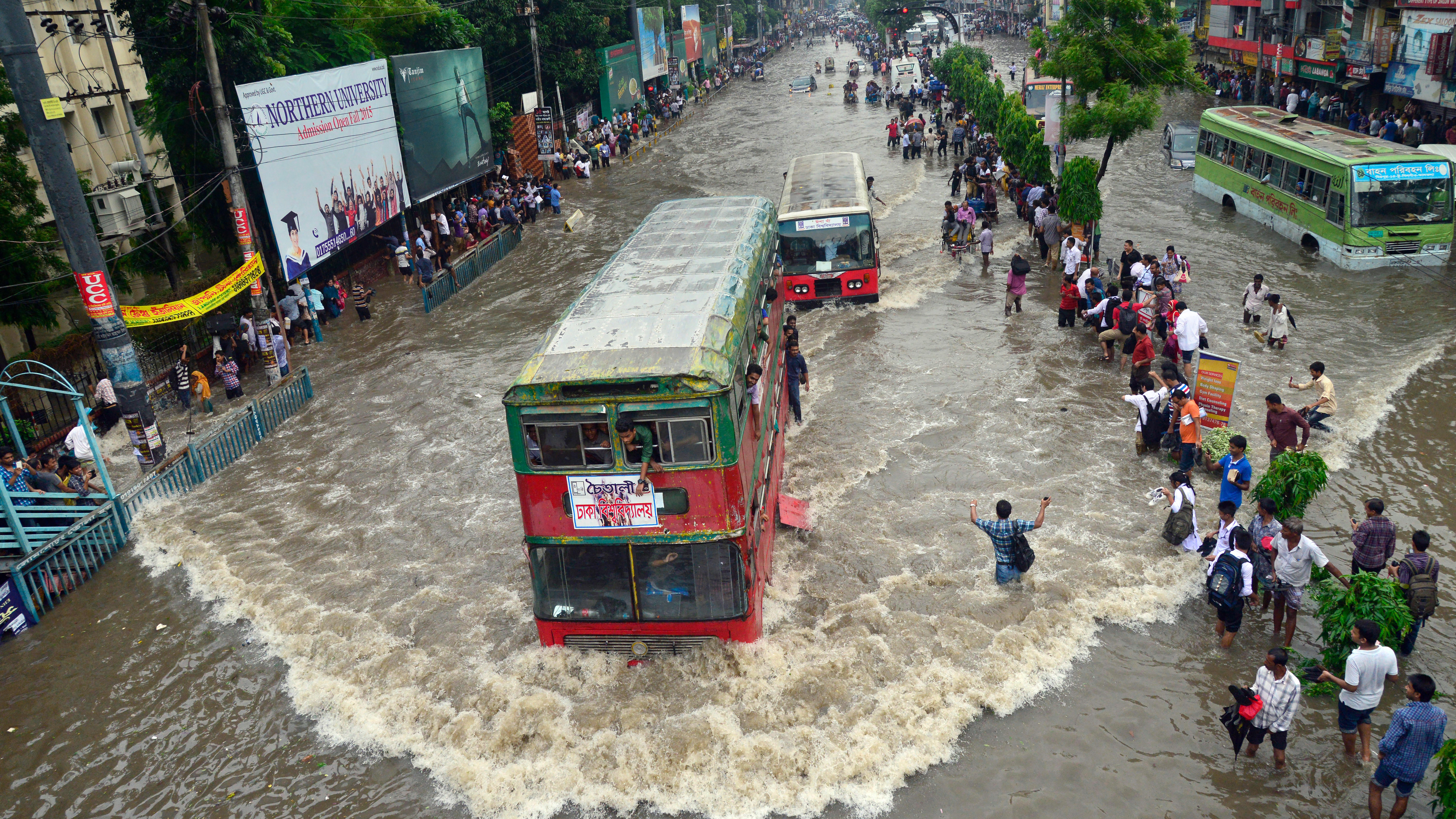 Vehicles try driving through the flooded Dhaka streets