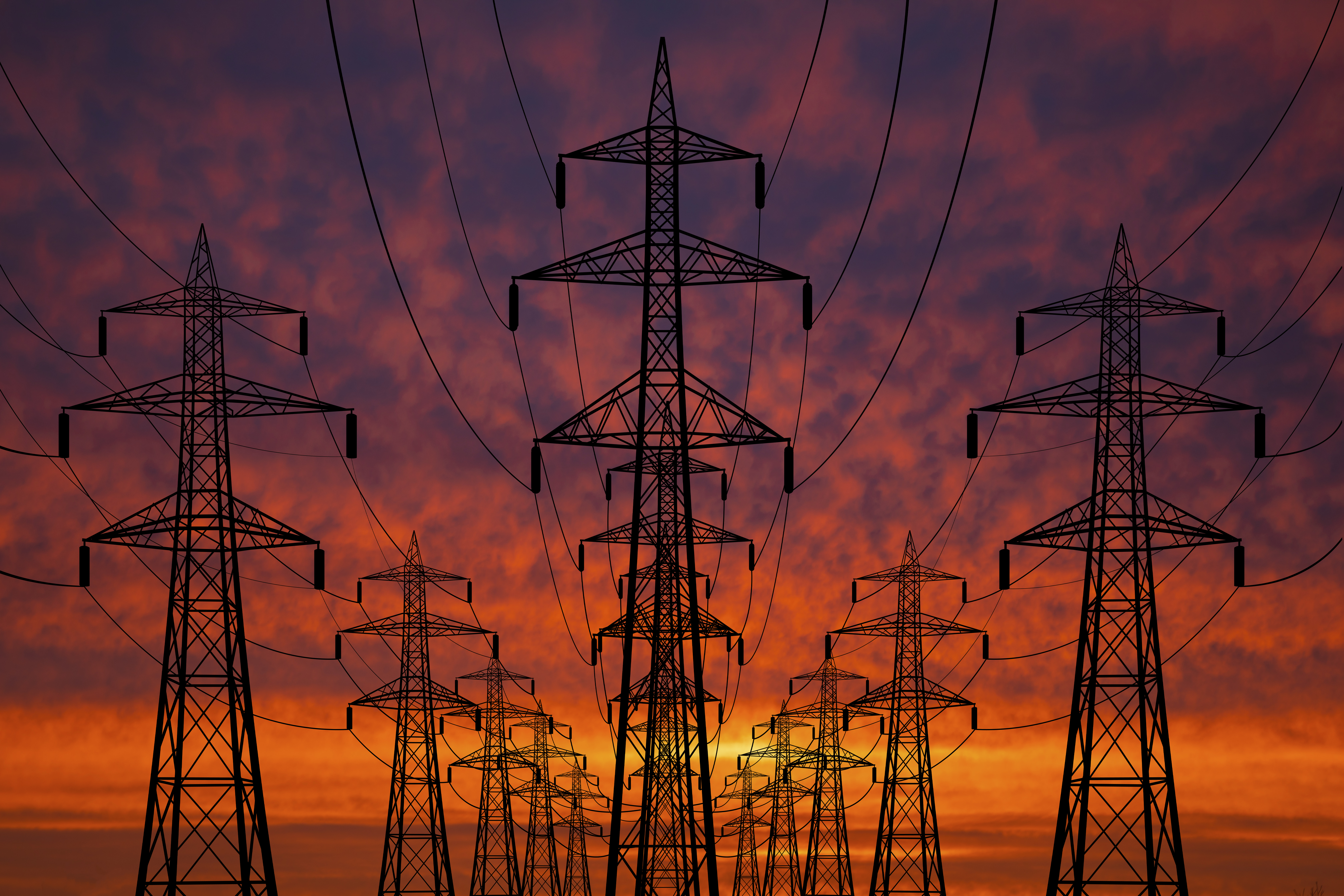 Photograph of High voltage towers at sunset. Power lines against the sky