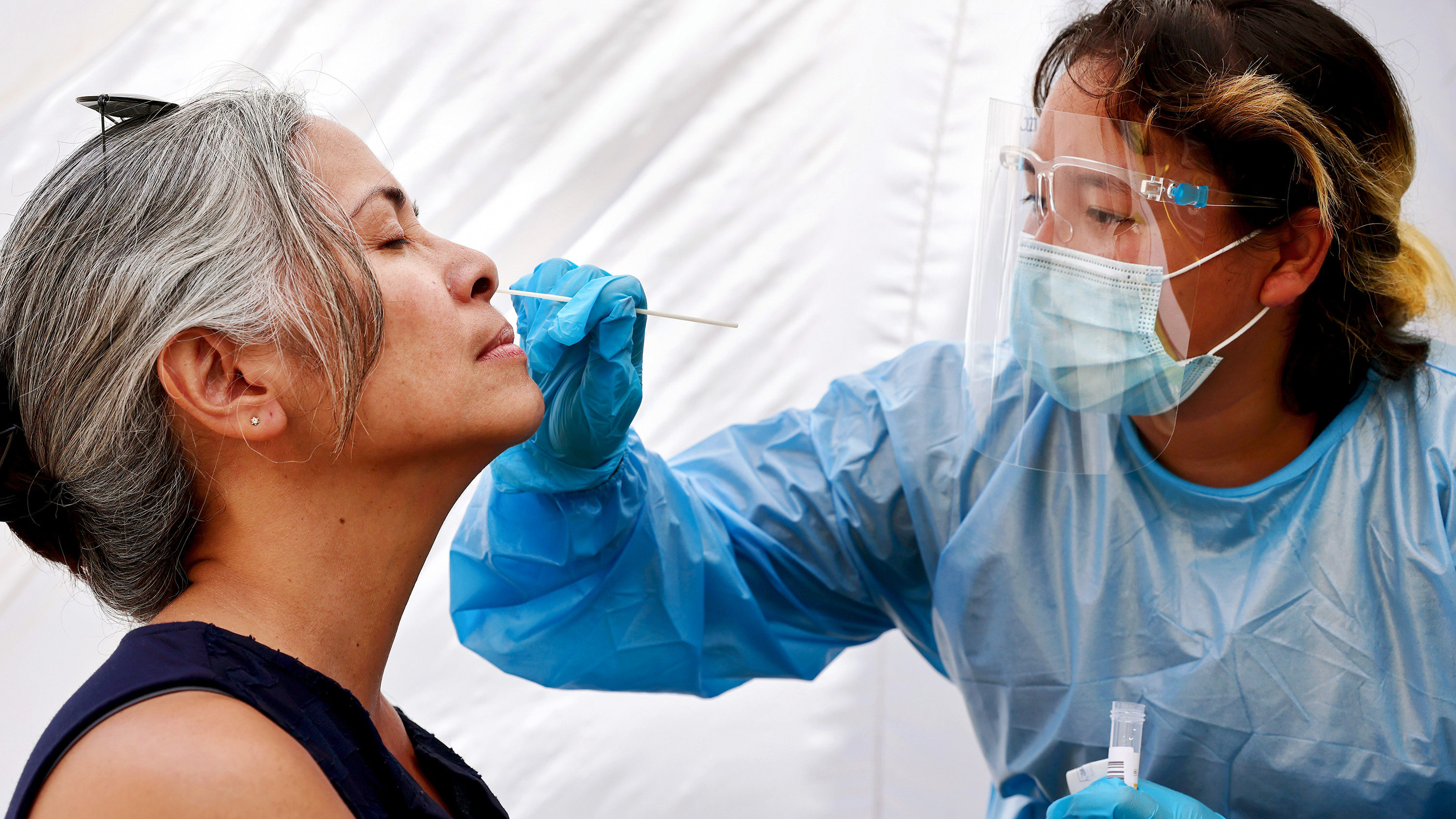 medical assistant administers a COVID-19 test in Los Angeles