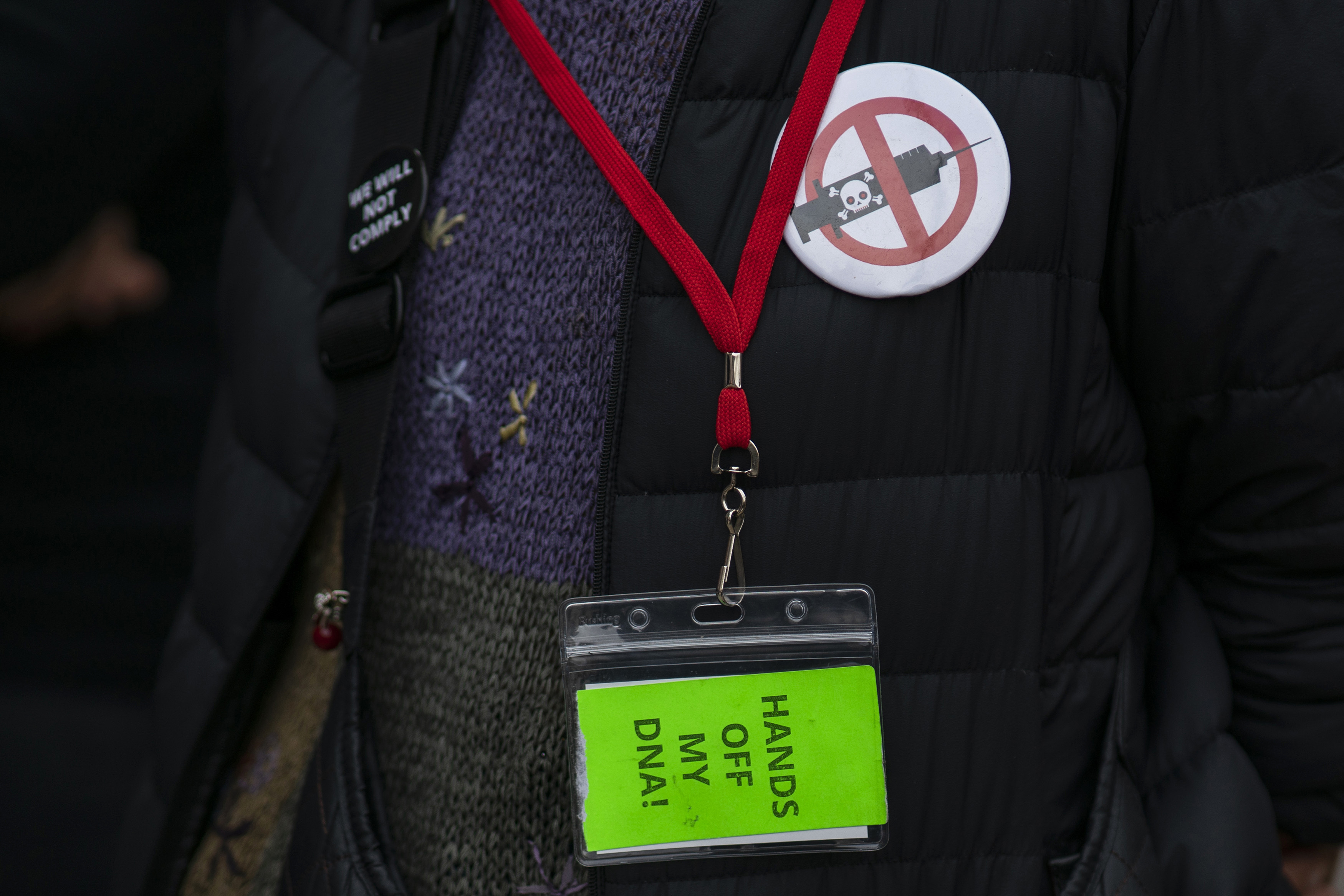 """photograph of someones badge saying """"hands off my dna!"""""""