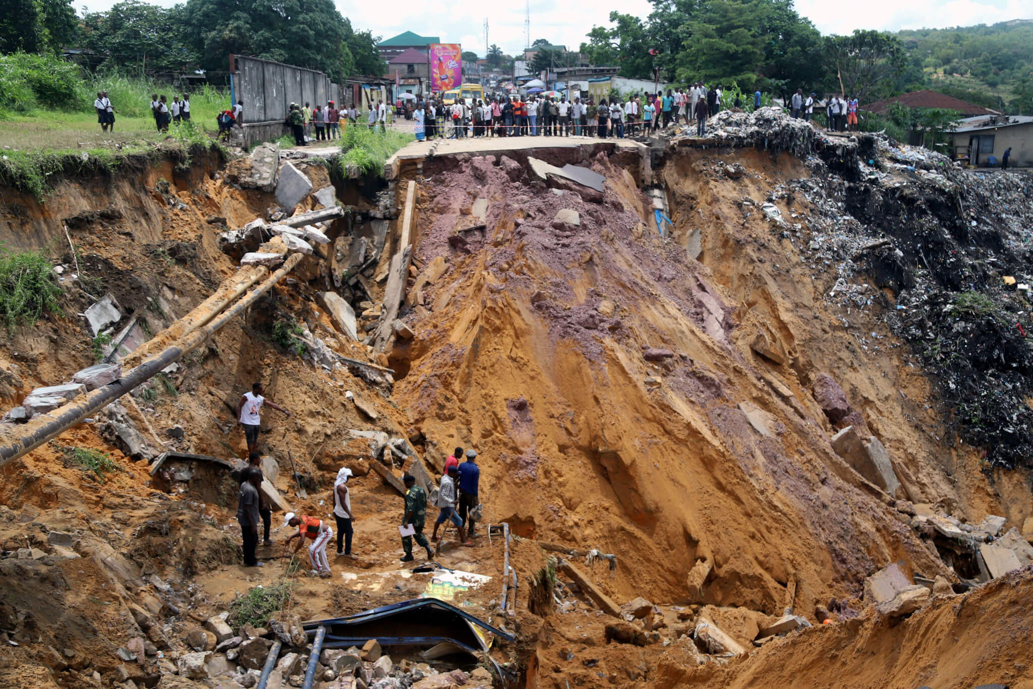 Residents of Kinshasa search for bodies in debris of landslide.